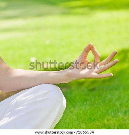 Woman hand during meditation outdoors.
