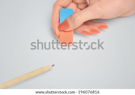 Woman hand erasing on table  - stock photo
