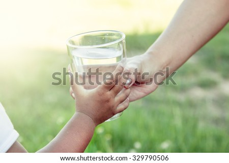 Woman hand giving glass of fresh water to child in the park,soft color filter - stock photo