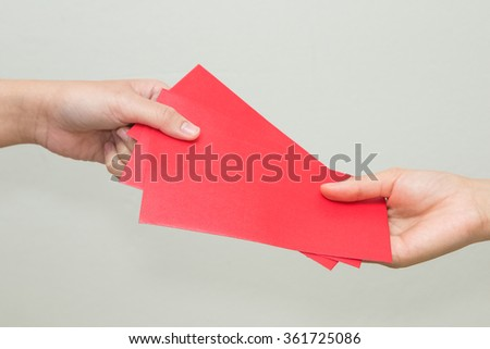 woman hand giving red envelop containing money, during Chinese New Year celebration  - stock photo