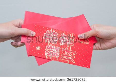 woman hand giving red envelop containing money, with Good Luck character, during Chinese New Year celebration  - stock photo