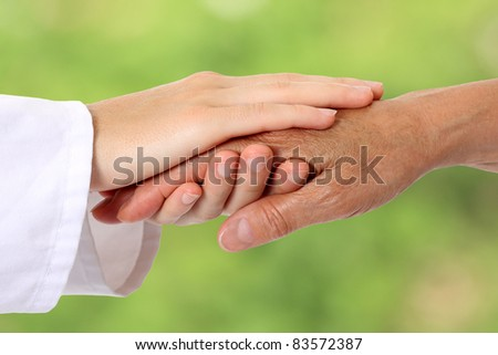Woman hand helping senior in nature - stock photo