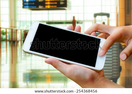 woman hand hold and touch screen smart phone,tablet,cellphone in the airport terminal - stock photo