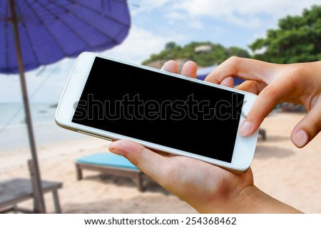 woman hand hold and touch screen smart phone, tablet,cellphone on blurred beautiful beach background.