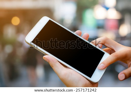 woman hand hold and touch screen smart phone,tablet,cellphone on shopping street background with sunset lighting.  - stock photo