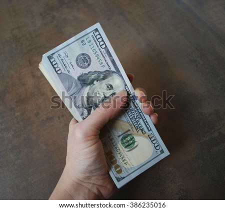 Woman hand hold cash dollar banknotes. Only hundreds. - stock photo