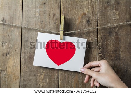 Woman Hand Hold Heart Photo in Frame Hanging on a Rope By Clothespin onWood Background , valentine concept - stock photo