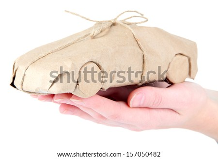 Woman hand holding a car wrapped in brown kraft paper, isolated on white - stock photo