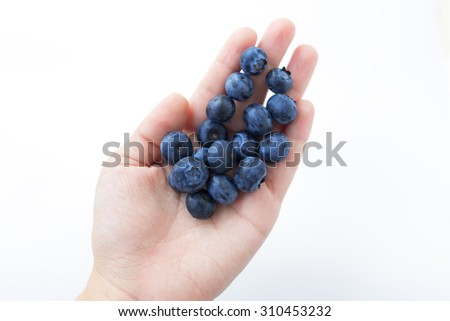 Woman hand holding a heap of blueberries.
