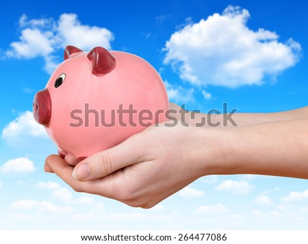 Woman hand holding a pink piggy bank - stock photo