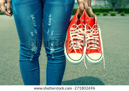 woman hand holding a red sneakers with vintage color. - stock photo