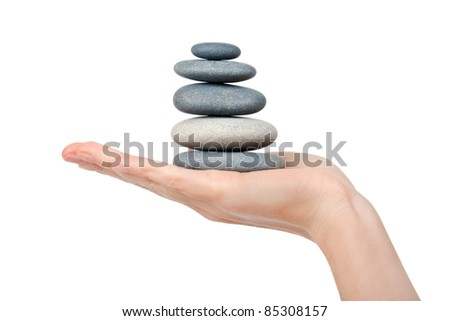 woman hand holding a stone tower isolated on white background - stock photo