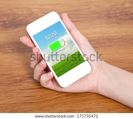 woman hand holding a touch white phone with charged battery on a screen against the background of a wooden table - stock photo