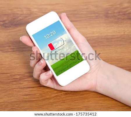 woman hand holding a touch white phone with low battery on a screen against the background of a wooden table - stock photo