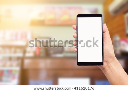 woman hand holding and using mobile (smart phone) over blurred image of restaurant background,Transactions by smartphone concept - stock photo
