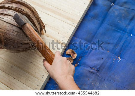 Woman hand holding ax with coconut on wooden background copy space