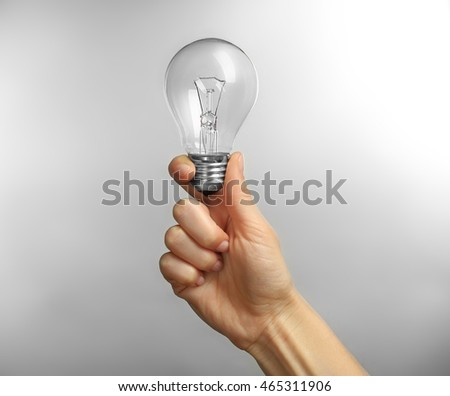 Woman hand holding bulb on grey background