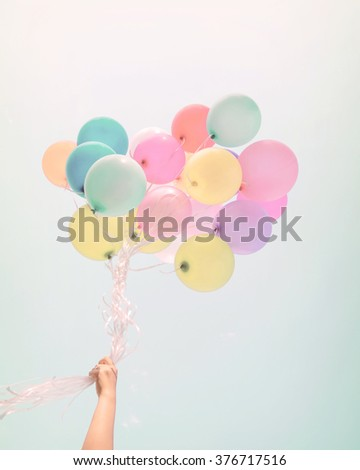 Woman hand holding colorful balloons. happy birthday party in summer holidays - pastel color filter - stock photo