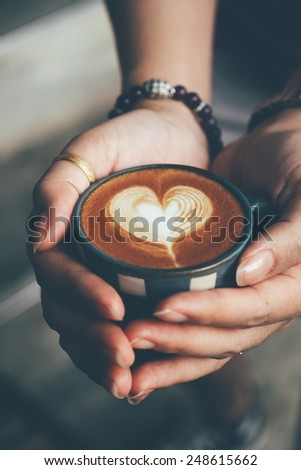 woman hand holding cup of coffee latte art in vintage color