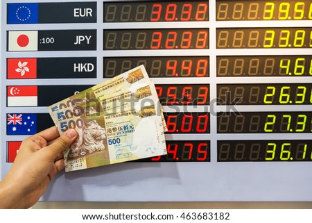 Woman hand holding Hong Kong dollar banknotes on currency exchange rate , digital LED exchange rate display board