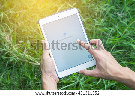 woman hand holding ipad mini 2 with Facebook messenger screen login on nature background. Bangkok,Thailand - July 12, 2016  - stock photo
