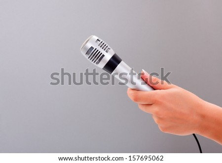 Woman hand holding microphone on gray background