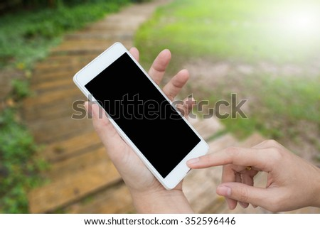 woman hand holding mobile/smart phone/cell phone/tablet over blurred image wood trail in the garden - stock photo