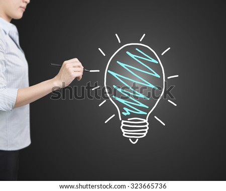 Woman hand holding pen drawing light bulb, side view, isolated on black background. - stock photo