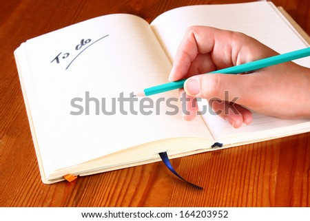 woman hand holding pencil and opened notebook with a to do list.  - stock photo