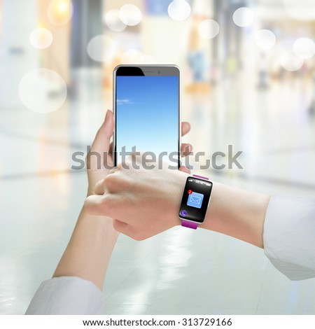 Woman hand holding smart phone and wearing smart watch with email icon on black touchscreen, on blur background.