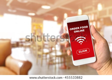 Woman hand holding smartphone against blur bokeh of coffee shop background with word order food online - stock photo