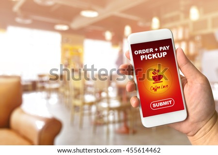 Woman hand holding smartphone against blur bokeh of coffee shop background with word order + pay + pickup coffee shop app concept - stock photo
