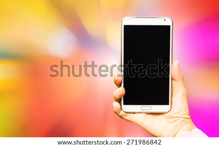 Woman hand holding smartphone against on brurry background soft focus. - stock photo