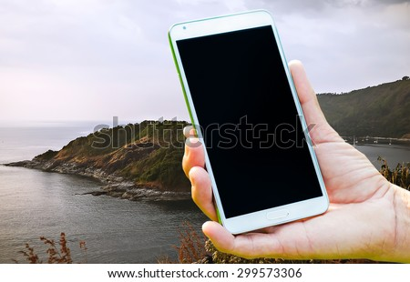 Woman hand holding smartphone against on nature of sea background soft focus. - stock photo