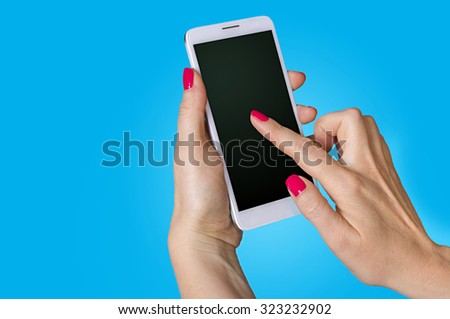 Woman hand holding the phone on blue background - stock photo