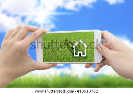 woman hand holding the phone with green grass and a house on the screen