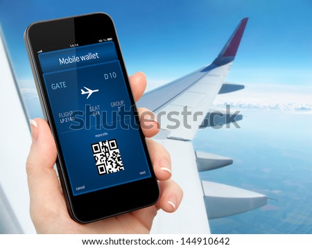 woman hand holding the phone with mobile wallet and plane ticket against the background of the window with blue sky and airplane wing - stock photo