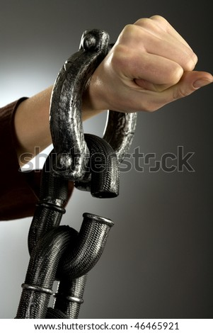 Woman hand in large handcuffs, gray background - stock photo
