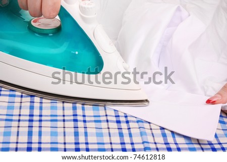 Woman hand ironing a shirt - stock photo