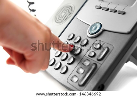 woman hand is dialing a phone number with picked up headset - stock photo