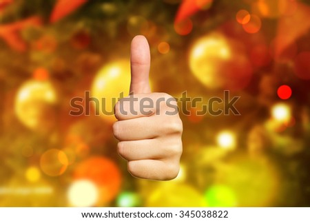 Woman hand making sign good. Woman hand with thumb up Isolated against Christmas or New Year tree.  - stock photo