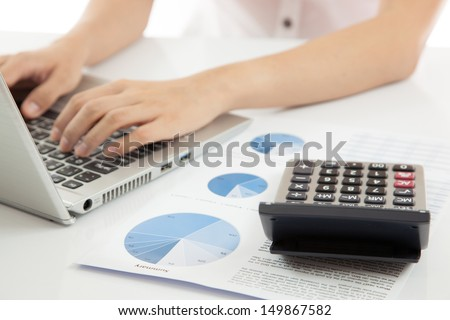 woman hand on laptop with business report and calculator - stock photo