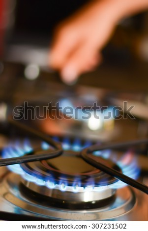 Woman hand opening a gas flame stove - stock photo