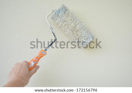 Woman  hand painting white wall - stock photo