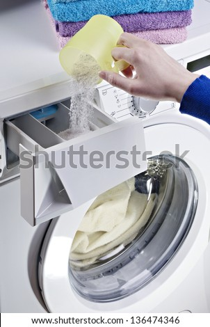 Woman hand pouring laundry detergent - stock photo