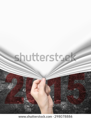 Woman hand pulling blank white curtain covered old 2015 text on dark mottled concrete wall. - stock photo