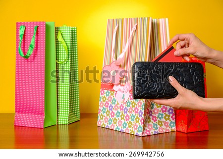 Woman hand pulling credit card out of black wallet - stock photo