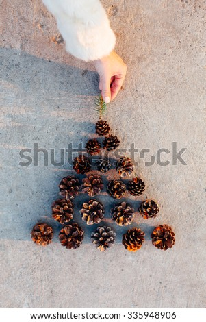 Woman hand puts a twig on the top of the tree of Pine cones - stock photo