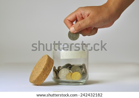 Woman Hand Putting a Coin into Glass Bottle  - stock photo
