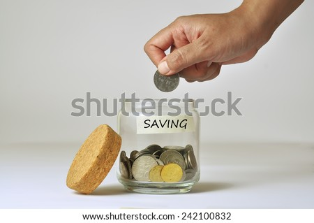 Woman Hand Putting a Coin into Glass Bottle for Saving - stock photo